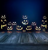pic of eerie  - Halloween pumpkins in a dark eerie background and wood floor - JPG