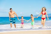 Happy Family Running and Playing on the Beach