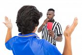 Referee showing red card to football player over white background
