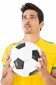 Handsome football player standing over white background