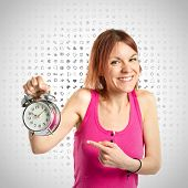 Happy Redhead Girl Holding A Clock Over Grey Background