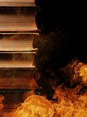 Conceptual image of a tall stack of hardcover books in a burning fire with flames and smoke swirling