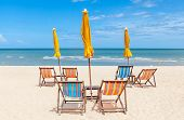 Beach Chairs And Sun Umbrellas On The White Sand Beach With Clear Blue Sky.