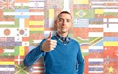 Man With Her Thumbs Up Over Flags Background