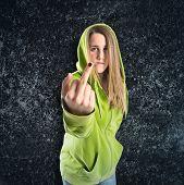 Girl Making Horn Gesture Over Black Background