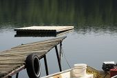 foto of dock a lake  - Wooden dock and raft in the water of a small calm lake - JPG