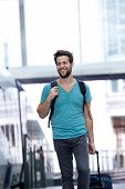 Smiling Man Walking With Bags At Train Station