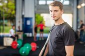 Portrait of confident fit man holding barbell bar at gym