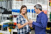Side view portrait of female customer receiving wrench from customer in hardware shop