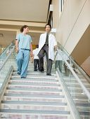 Low angle view of female nurse and doctor walking down stairs in hospital