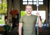 Portrait of smiling male athlete holding weightlifting bar at gym