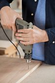 Midsection of young carpenter drilling wood in workshop
