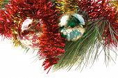 metallic christmas holiday toys with shiny red garland on fir tree twig isolated over white backgrou