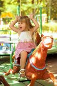 foto of merry-go-round  - Happy beautiful girl on a colorful merry - JPG
