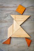 stock photo of tangram  - abstract of a dancing or walking figure built from seven tangram wooden pieces - JPG
