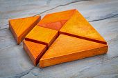 seven tangram wooden pieces, a traditional Chinese puzzle game, slate rock background