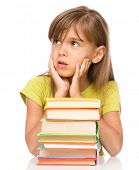 Little girl and a pile of books supporting her head with hands, isolated over white