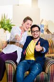 Young couple selecting together armchair in furniture store