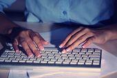Female hands typing on keyboard, on dark background