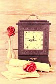 Still life with old retro clock on wooden background