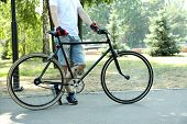Young man riding bike in city park