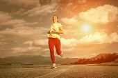 Beautiful female running on road under sky with sun light