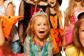 stock photo of happy halloween  - Little laughing girl wearing dress crown surrounded by friends kids in Halloween costumes - JPG