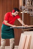 Young male carpenter using bandsaw to cut wooden plank in workshop