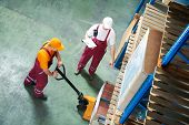 stock photo of lift truck  - workers with fork pallet truck stacker in warehouse loading furniture panels - JPG