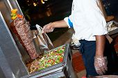 Arab chef in cook uniform making kebab with meat and vegetables