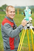 stock photo of theodolite  - One surveyor worker working with theodolite transit equipment at spring field construction site outdoors - JPG