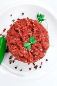 very big raw hamburger cutlet with sprouts and chili pepper on white plate isolated over white backg