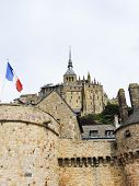 Flag And Abbey Mont Saint-michel In Normandy