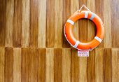 The Orange Life Buoy With The Wood Wall Background, For Safety And Rescue