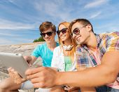 friendship, leisure, summer and people concept - group of smiling friends with tablet pc computers sitting outdoors