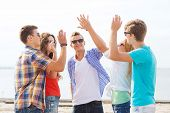 friendship, leisure, summer, gesture and people concept - group of smiling friends making high five
