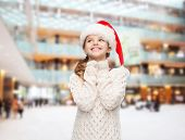 christmas, holidays, childhood and people concept - smiling girl in santa helper hat over shopping c