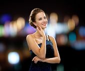 people, holidays and glamour concept - smiling woman in evening dress over black background over nig