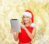 christmas, technology, present and people concept - smiling woman in santa helper hat with tablet pc