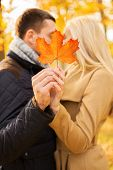 love, relationship, family and people concept - close up of couple with maple leaf kissing in autumn