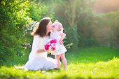 Happy Mother And Her Daughter In The Garden
