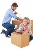 Young couple packing moving boxes against white background