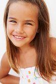 Portrait Of Pretty Hispanic Girl Standing By Wall
