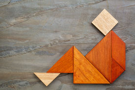 picture of tangram  - abstract sitting or relaxing figure built from seven tangram wooden pieces - JPG
