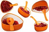 Natural Pomegranate seeds in orange cup with spoon