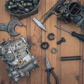 stock photo of carburetor  - Carburetors for a car engine with tools on wooden table - JPG