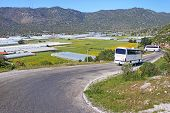 Glasshouses With Plastic And Touristic Buses Near Village In Turkey