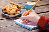 pic of office romance  - Female hand writing something in note near cookie and cup of coffee - JPG