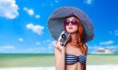 Redhead Girl With Retro Camera On The Beach