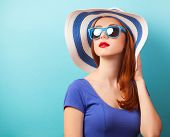 foto of redhead  - Redhead girl with sunglasses and hat on blue background - JPG